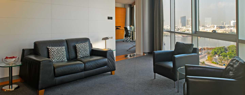 Hotel Hilton Dubai Creek, Emirati Arabi Uniti – Zona soggiorno della suite Deluxe con letto king size